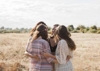 Boho women hugging in rural field